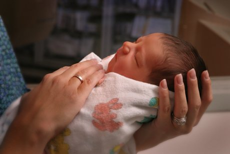 Newborn being held by nurse