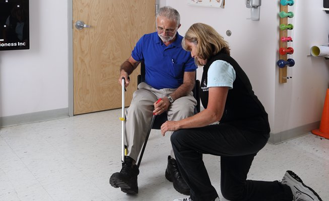 occupational therapist helping man with shoes