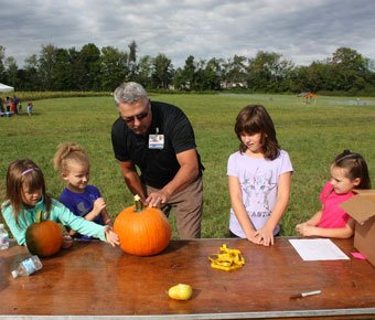 Man coloring pumpkin with kids