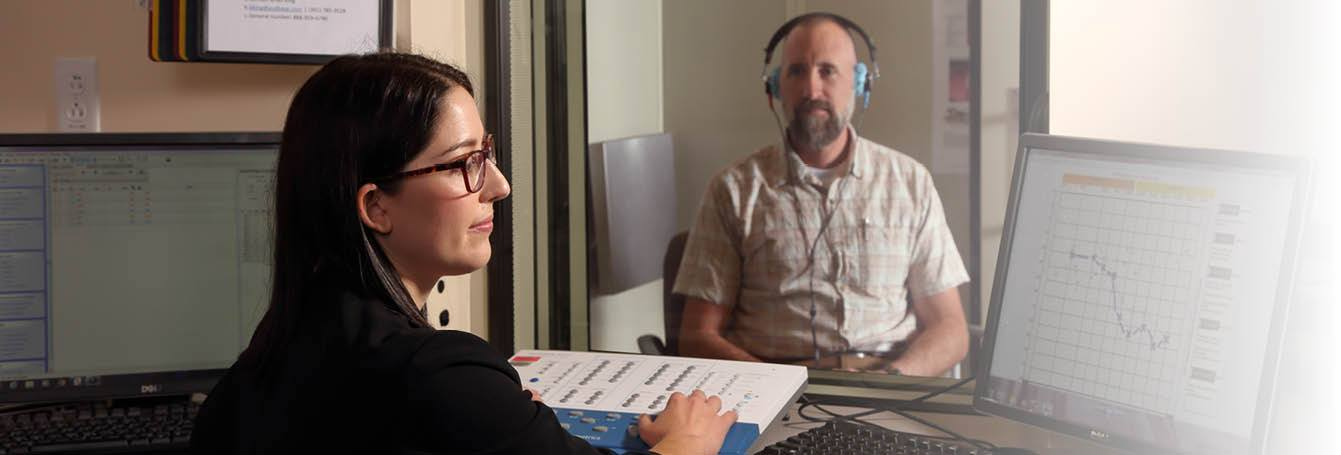 female audiologist working with male patient in sound booth
