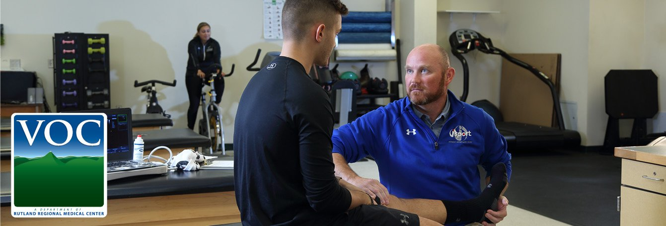 Physician examining injured athlete in athletic trainer room