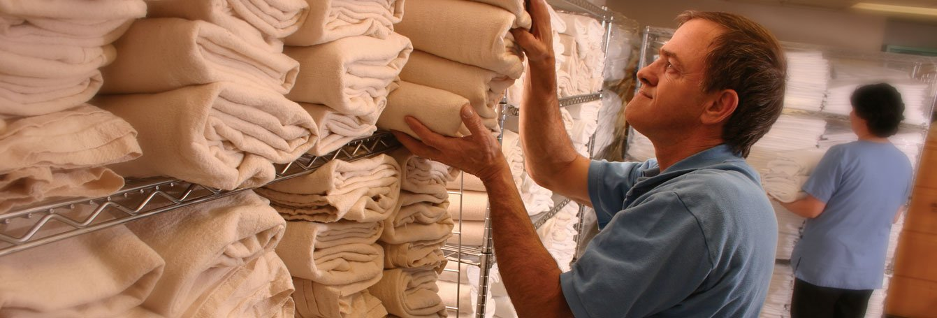 man stacking linens