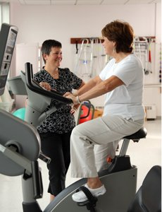 Physical Therapist working with patient on stationery bike