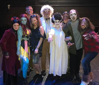 nine employees in costume for a lip sync battle