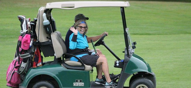 woman waving from golf cart