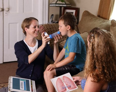 Asthma educator instructing child how to use inhaler