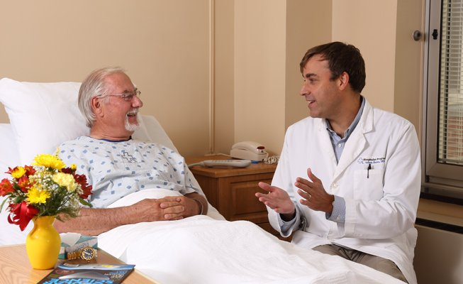 Hospitalist talking with a patient in a bed